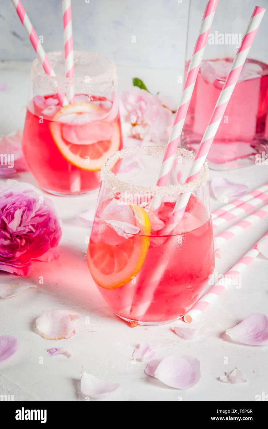 Estate bevande ristoro. Luce rosa rosa cocktail con vino rosato, tè petali di rosa, limone. Su una pietra bianca Immagini Stock