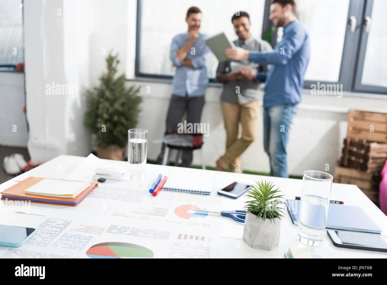 Vista ravvicinata di grafici aziendali e delle forniture di ufficio sulla scrivania e di imprenditori in piedi dietro, Immagini Stock