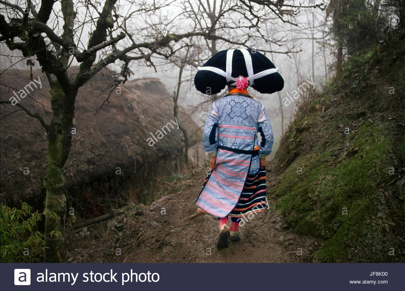 Una donna dalla lunga cornuto Miao minoranza etnica su un sentiero a piedi si prepara per il Lusheng Festa della Immagini Stock