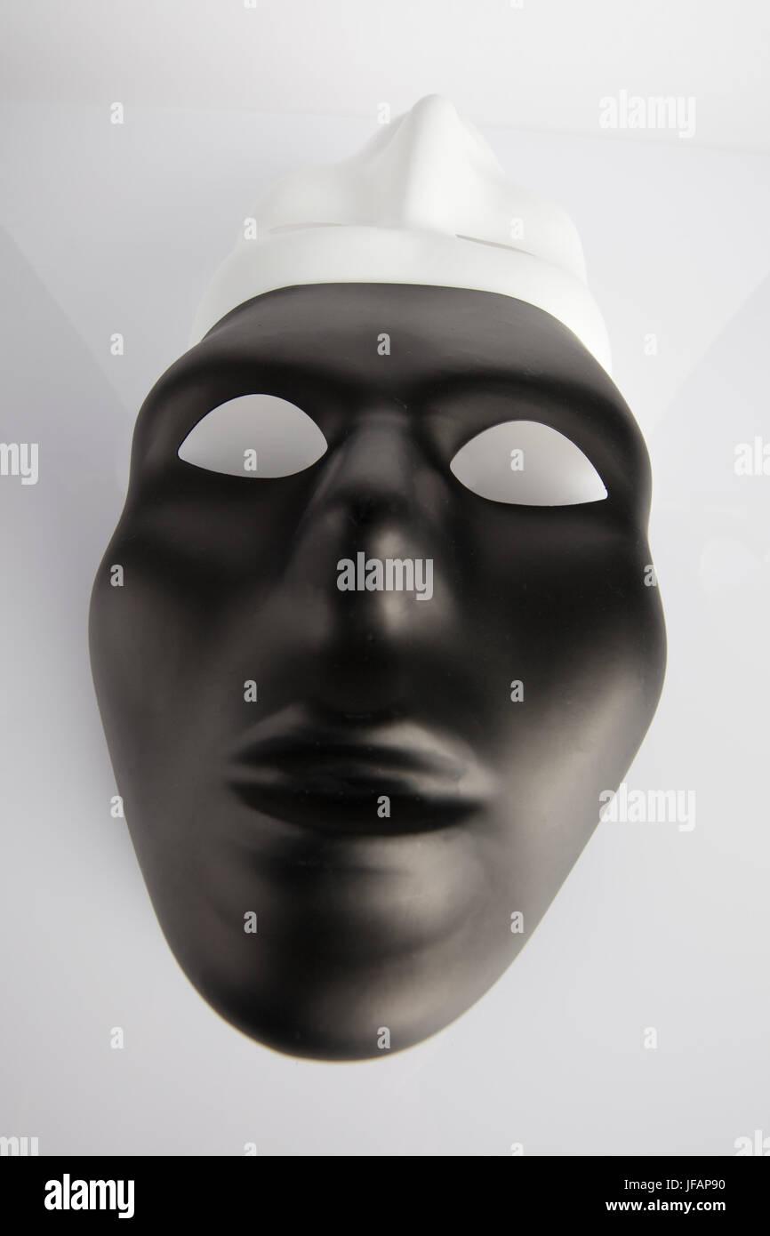 Bianco e nero maschere unita su bianco sfondo riflettente. Grandangolo, l'immagine verticale, vista dall'alto. Foto Stock