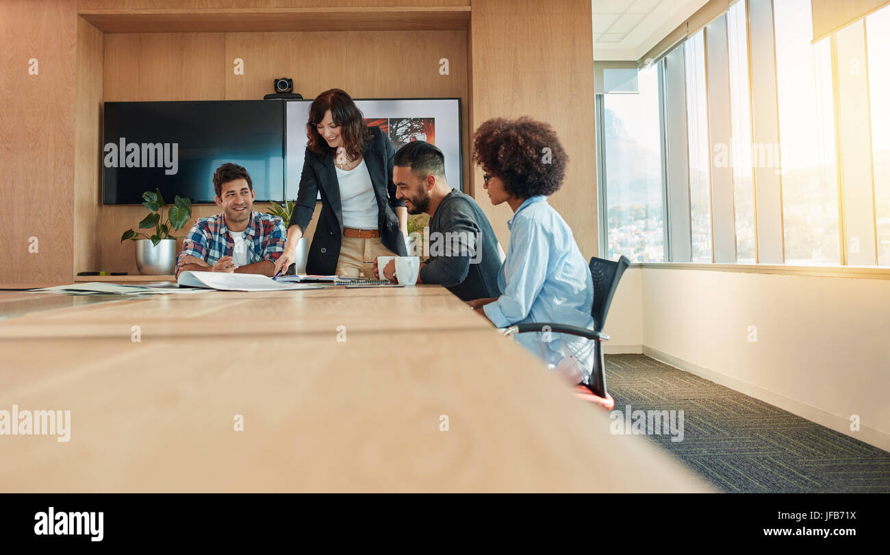 Multi etnico gruppo di giovani uomini di affari che incontro in sala conferenze. Team di professionisti creativi Foto Stock