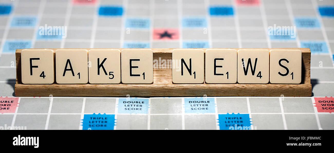 """Un gioco SCRABBLE board con le lettere che compongono le parole """"Fake News'. Scrabble è un gioco divertente Immagini Stock"""