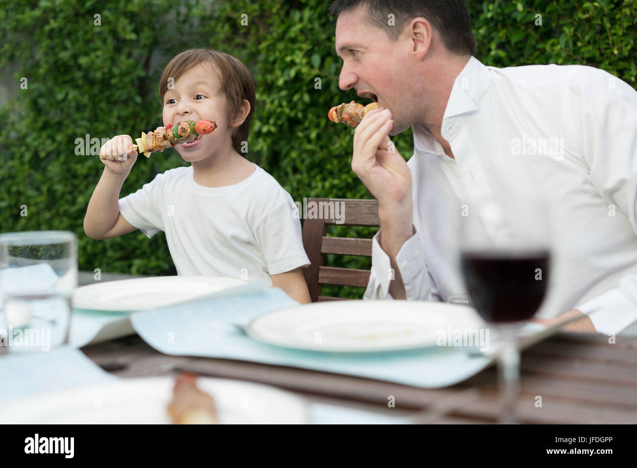 Padre con piccolo ragazzo bcute mangiare barbecue in famiglia ora di pranzo a casa. Immagini Stock