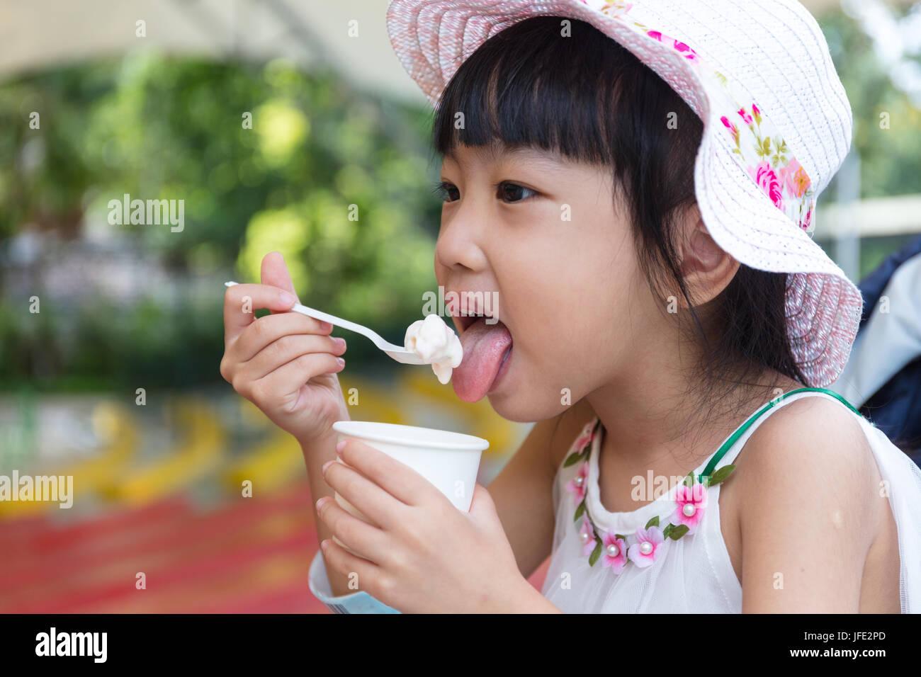 Cinese asiatici bambina a mangiare il gelato al parco all'aperto Foto Stock