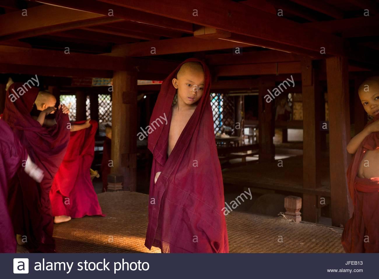 Giovani monaci stand in rosso scuro vesti la Shwe Chan Thar monastero. Immagini Stock