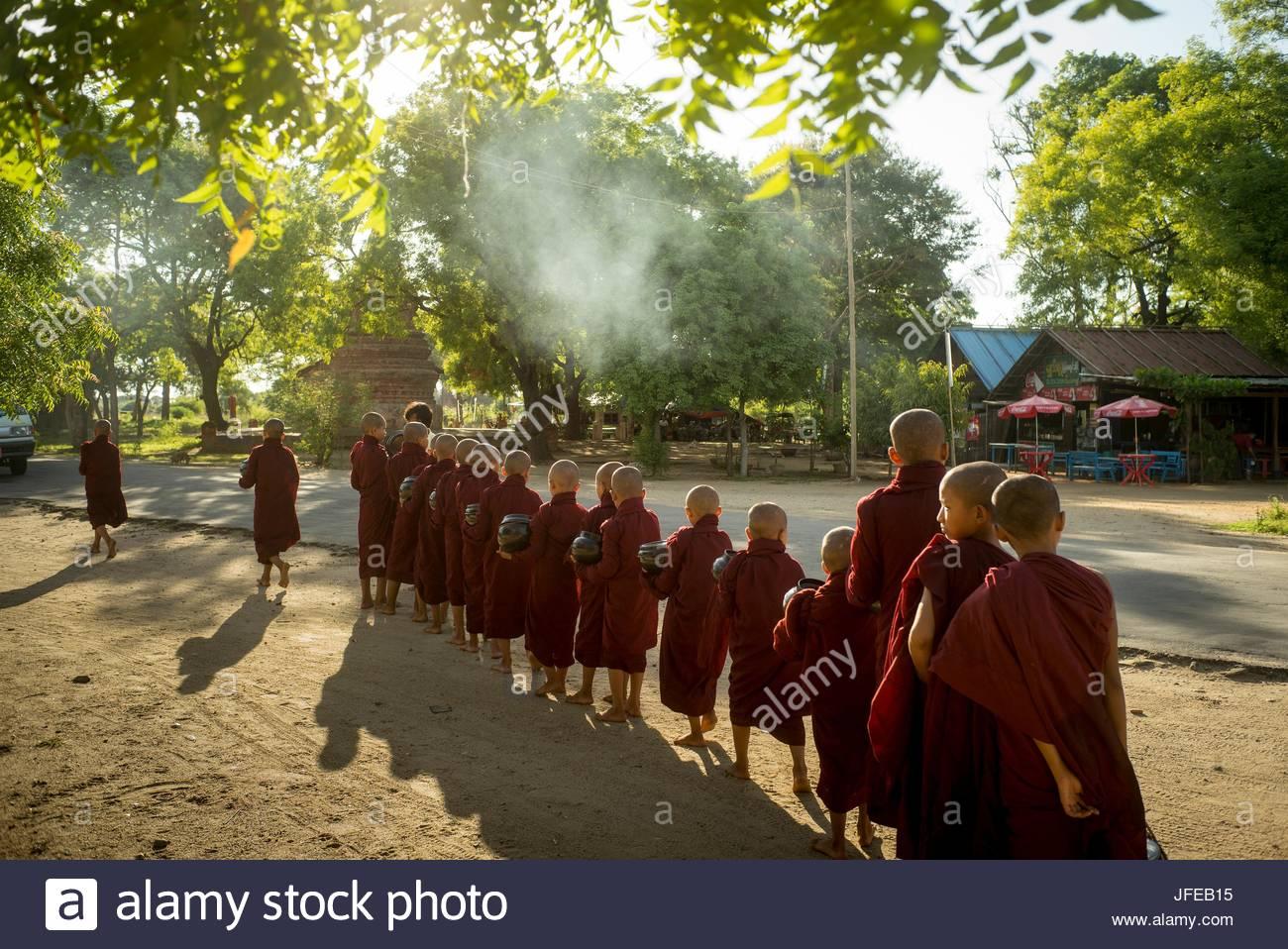 Giovani monaci stand in una linea azienda accattonaggio bocce Shwe Chan Thar monastero. Immagini Stock