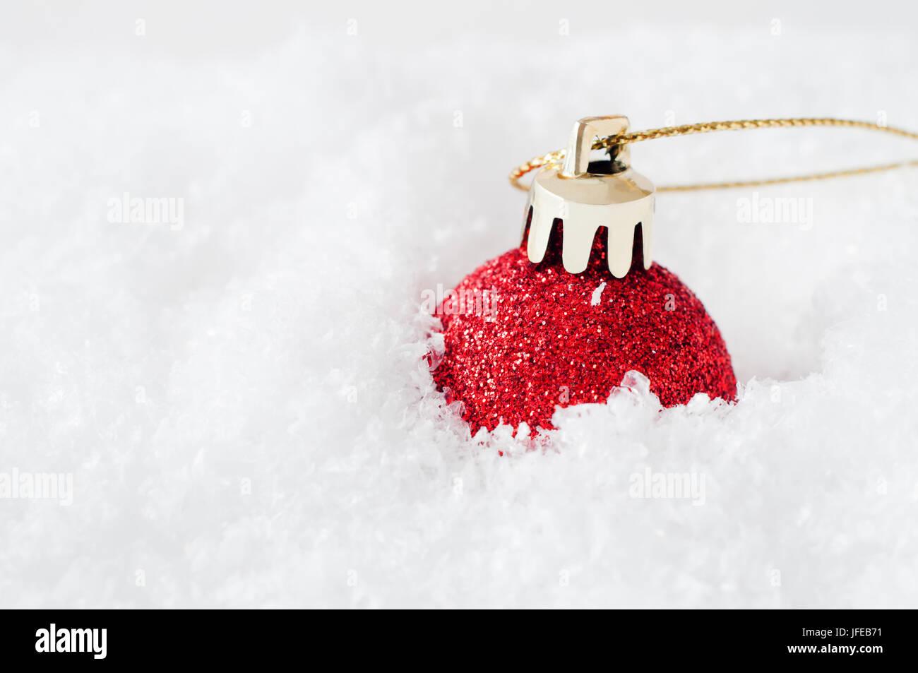 Un vivace colore rosso glitter natale Pallina, con fibbia in oro e dorate di stringa, affondato in finto bianco Immagini Stock