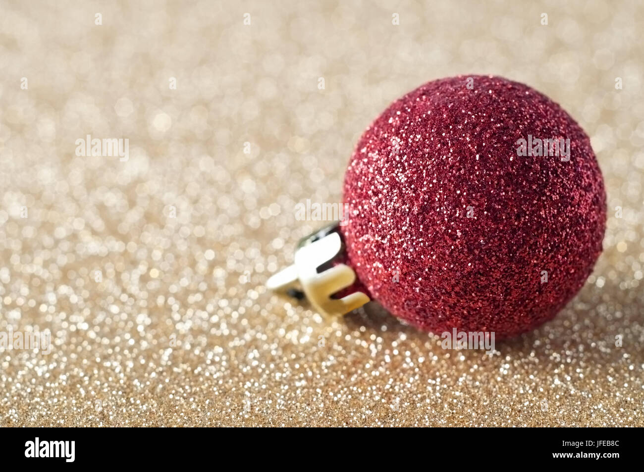 Un singolo, rosso scintillanti ninnolo, rivestito in glitter, appoggiato su un gold glitter sfondo che si ammorbidisce Immagini Stock