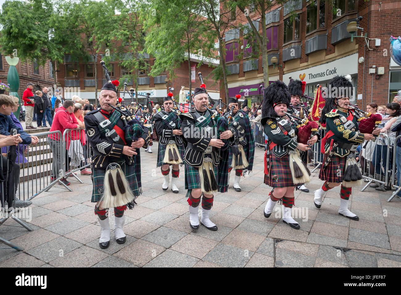 Pipers nel Northenden Pipe Band marciando attraverso il centro della città su Warrington camminare giorno Foto Stock
