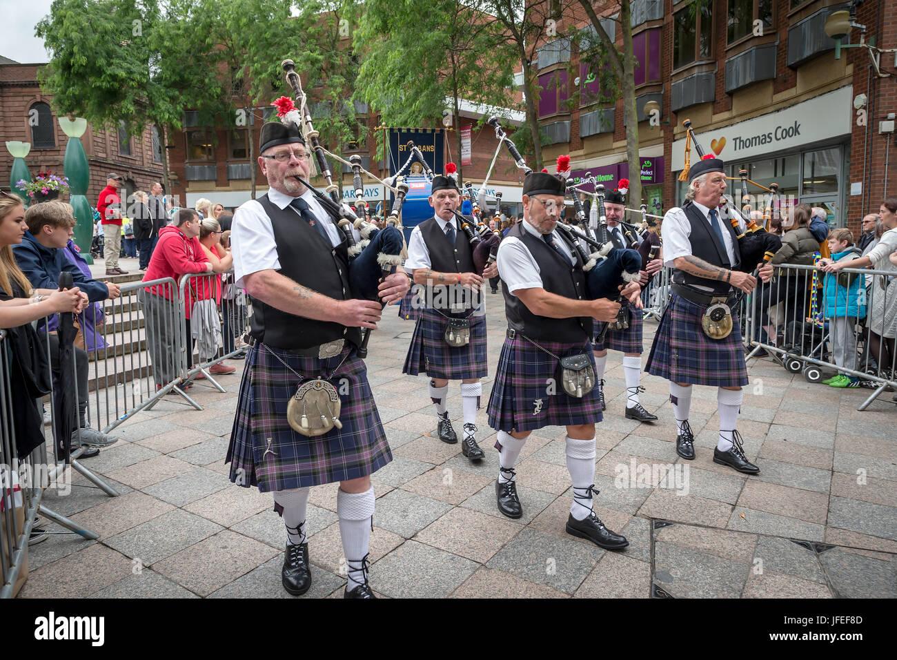 Pipers in Oldham Scottish Pipe Band marciando attraverso il centro della città su Warrington camminare giorno Foto Stock
