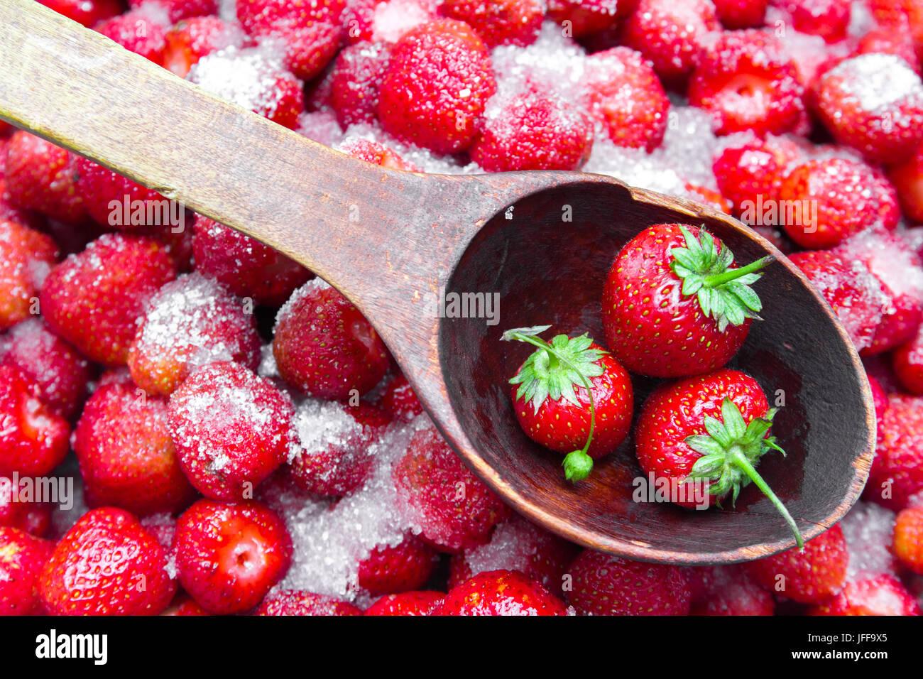 In un contesto di fragole lo zucchero con un cucchiaio di legno per inceppamento sulla quale si trova un paio di Immagini Stock