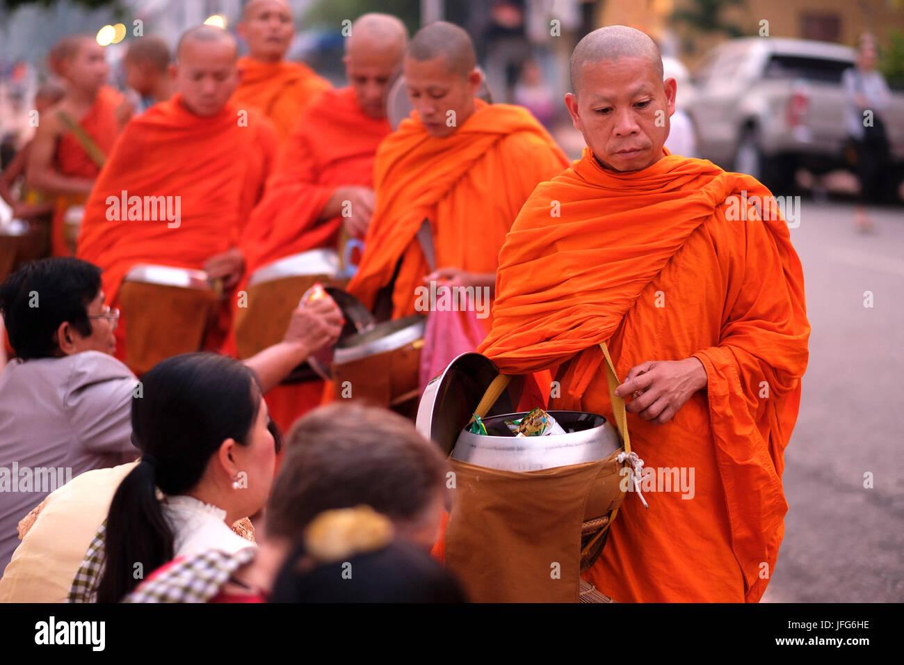 Processione di monaci buddisti che indossa arancione vesti all'alba per raccogliere doni per le strade di Luang Foto Stock