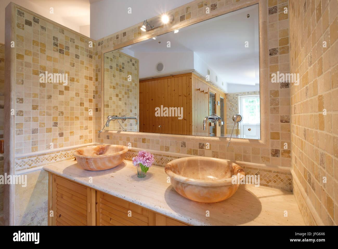Bagno con doppi lavandini luce piastrelle gialle e un grande