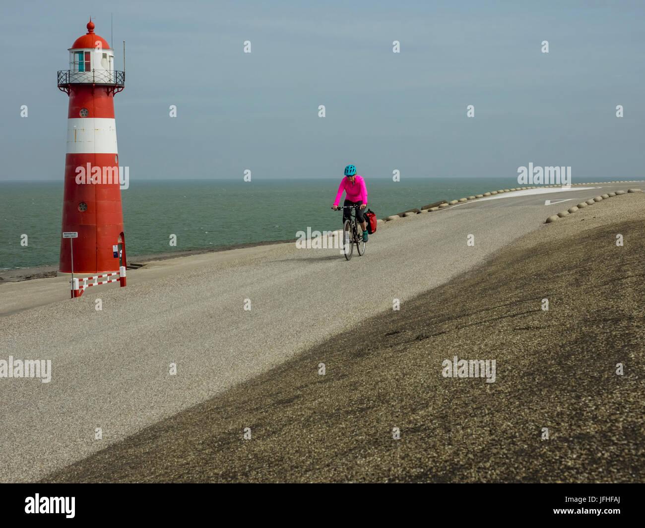Equitazione donna bici su strada per mare Immagini Stock