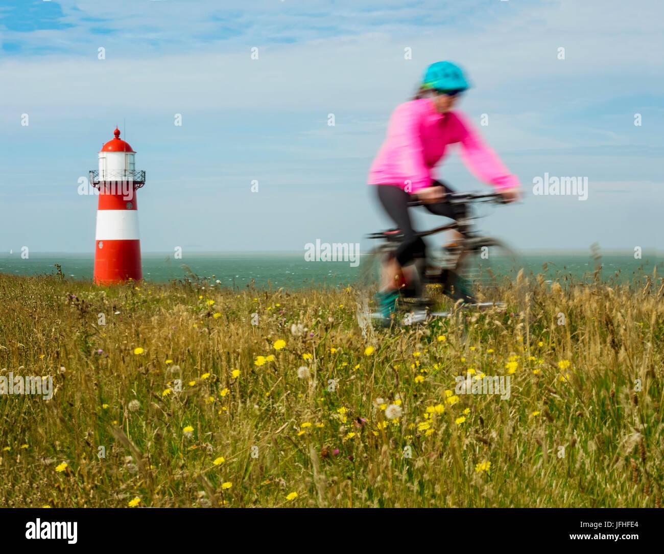 Equitazione donna bici sul campo nei pressi di faro Immagini Stock