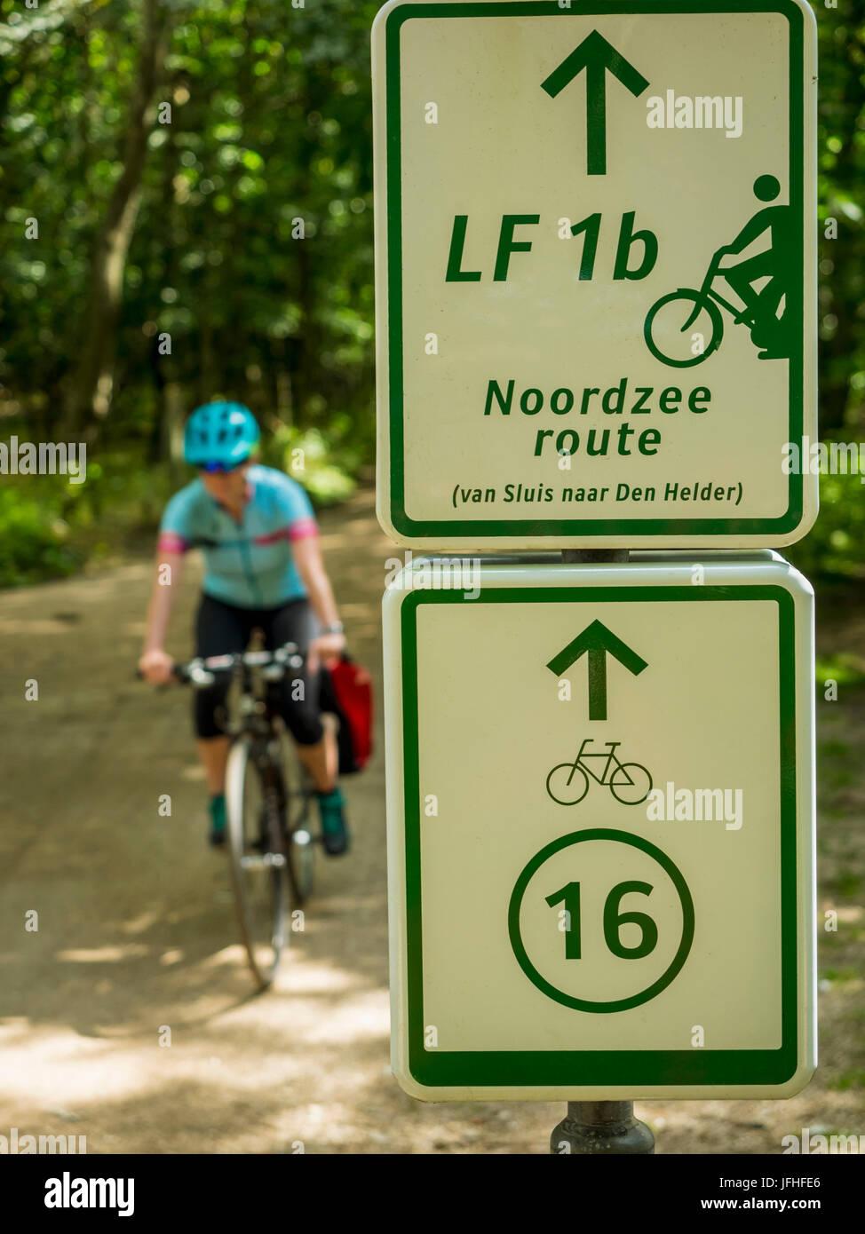 Close-up di segno di bicicletta e il ciclista in sella Immagini Stock