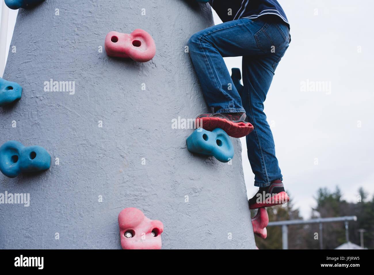 Un ragazzo si arrampica attrezzature per parchi giochi. Immagini Stock