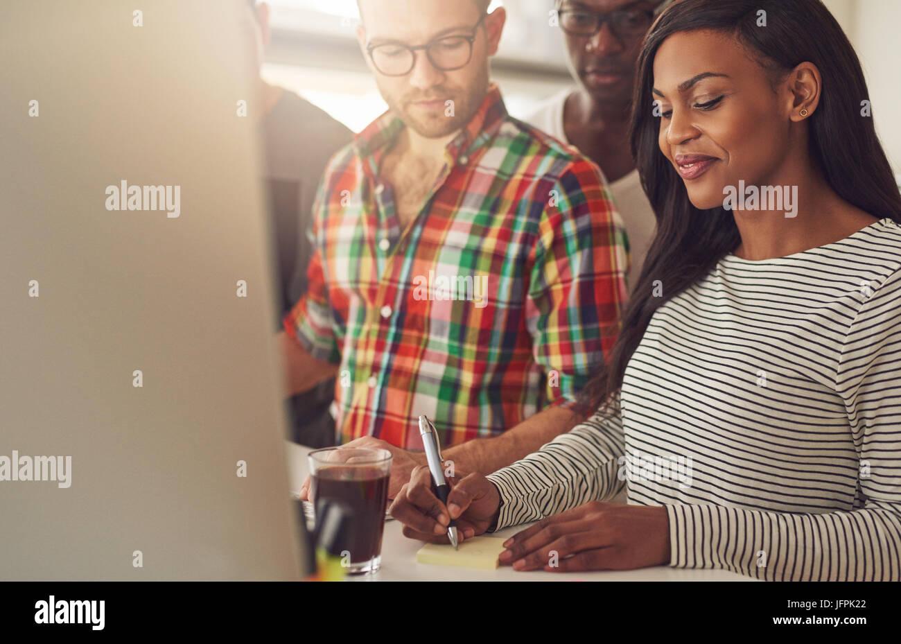 Giovane donna prendendo una nota mentre la gente guarda al suo in ufficio. Immagini Stock