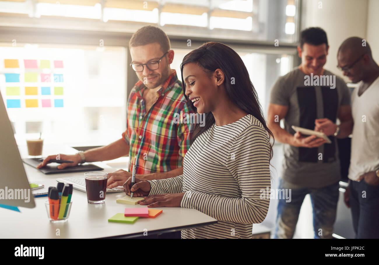 Giovane donna prendendo le note con un collega mentre la navigazione degli utenti di tablet in ufficio. Immagini Stock