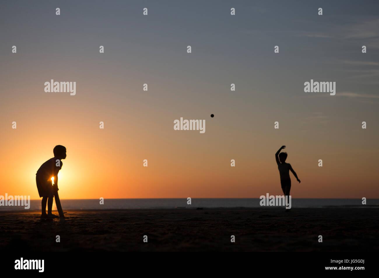 Due ragazzi giocare a cricket sulla spiaggia al tramonto, DEVON REGNO UNITO Immagini Stock