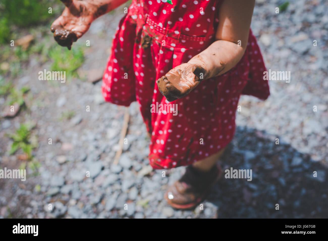 Un bambino con le mani in mano sono ricoperte di fango Immagini Stock