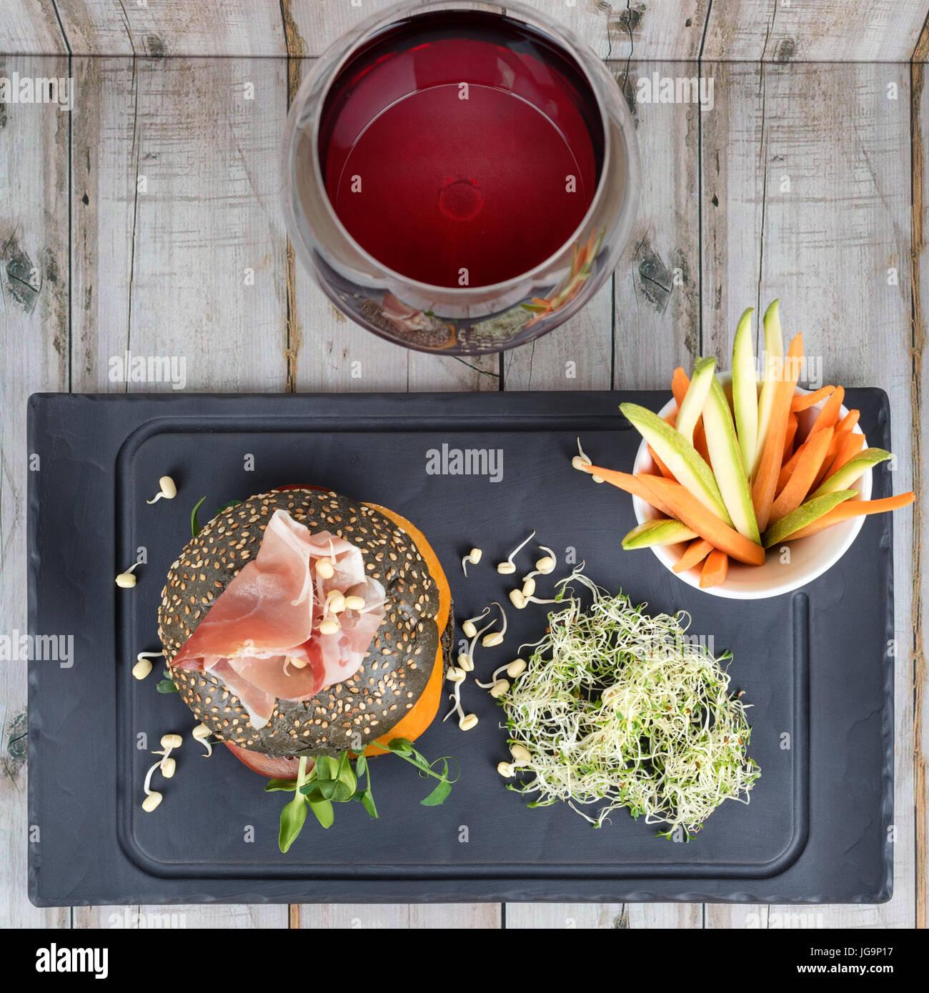 Un sano hamburger con hamon, pomodori, micro verde e nero panini integrali, bastoncini di verdure e vino rosso su Immagini Stock