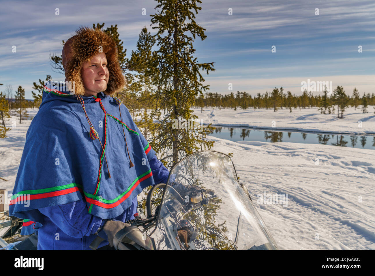 L uomo nel tradizionale abito Sami su una motoslitta, Lapponia, Svezia Immagini Stock