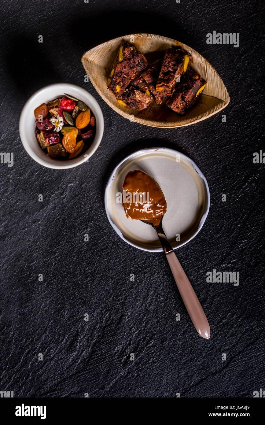 Dulce de leche in un cucchiaio, molto dolce creme caramel o pralina creme da Argentina e alcuni biscotti al cioccolato Immagini Stock