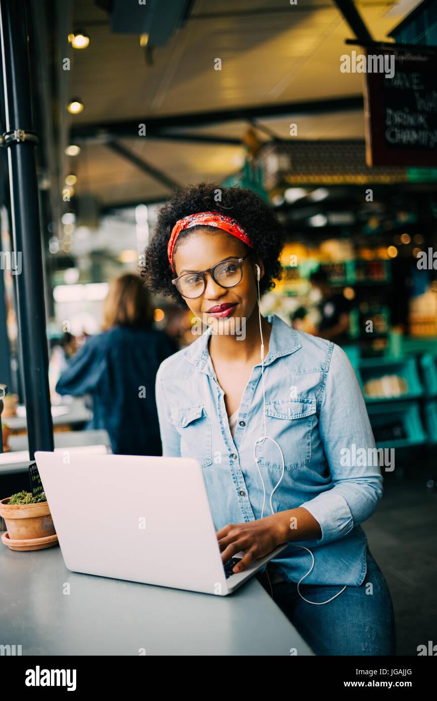 Sorridente giovane donna africana seduto da solo ad un contatore in un bistro lavorando su un computer portatile e di ascoltare la musica in cuffia Foto Stock