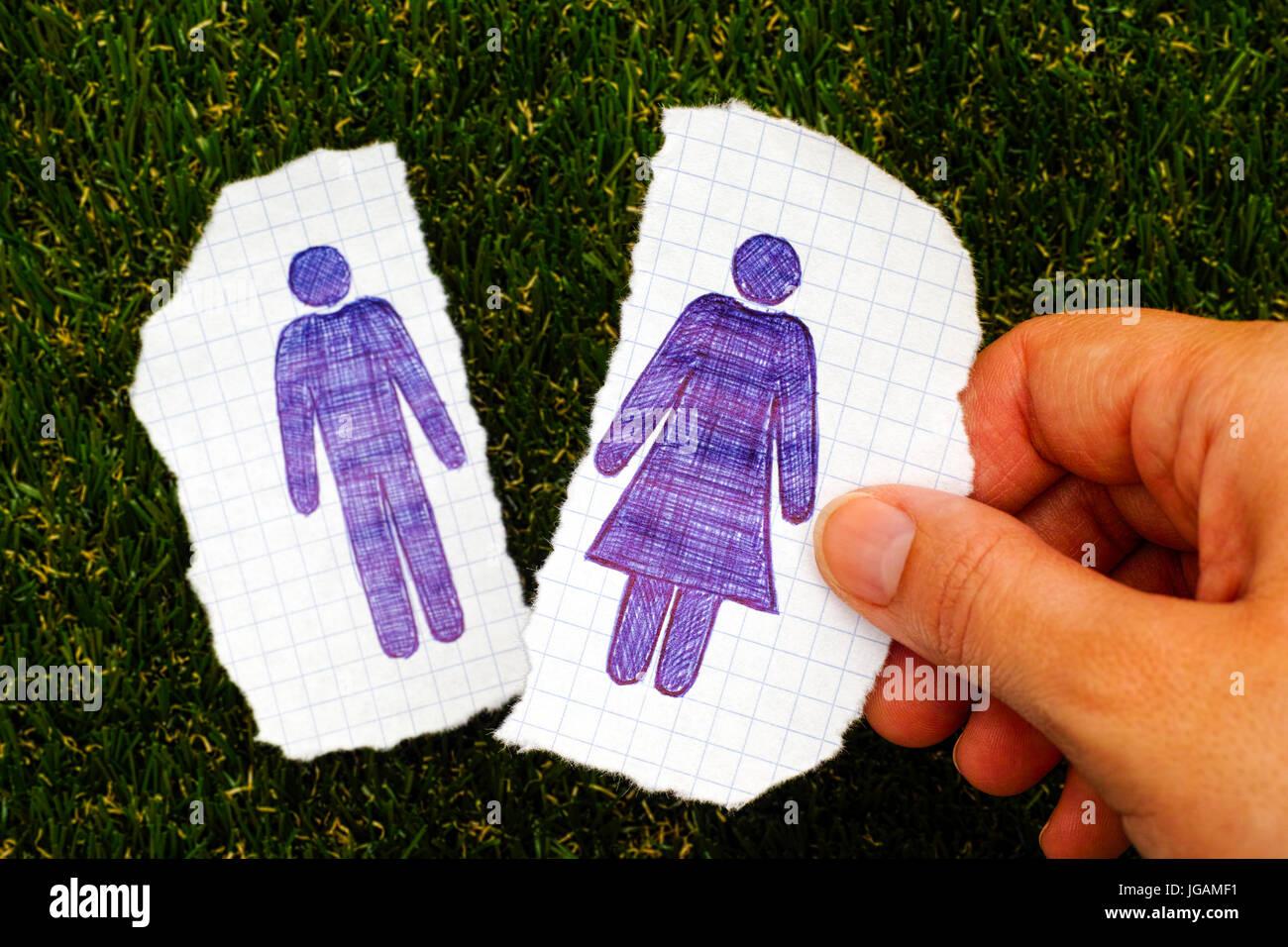 La persona tenuta a mano pezzo di carta con disegnati a mano donna figura. Altro pezzo di carta con uomo disegnata Immagini Stock