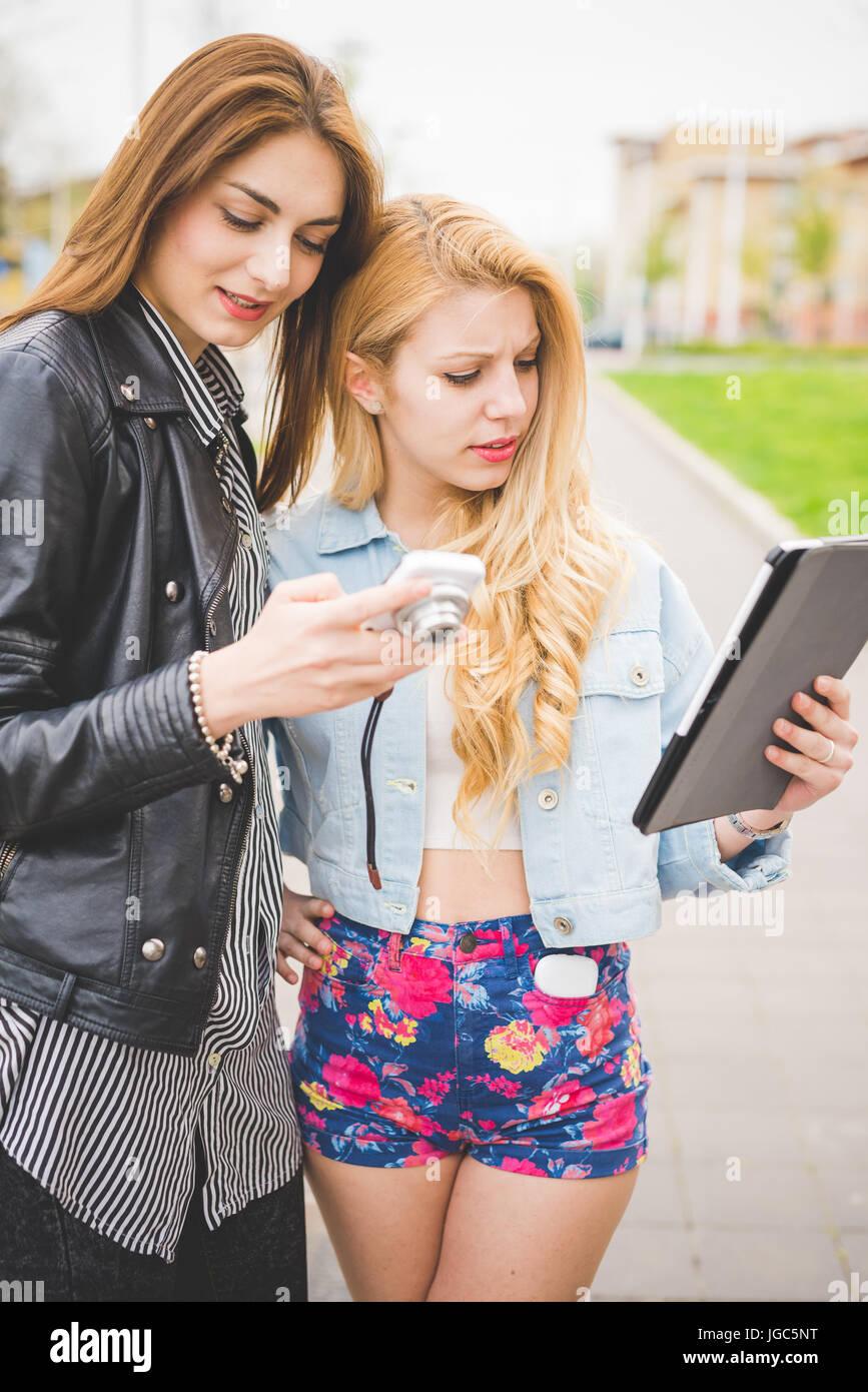 Due giovani bionda e bruna le ragazze a piedi attraverso la città  utilizzando una compressa e una fotocamera - tecnologia a4378fd6320e