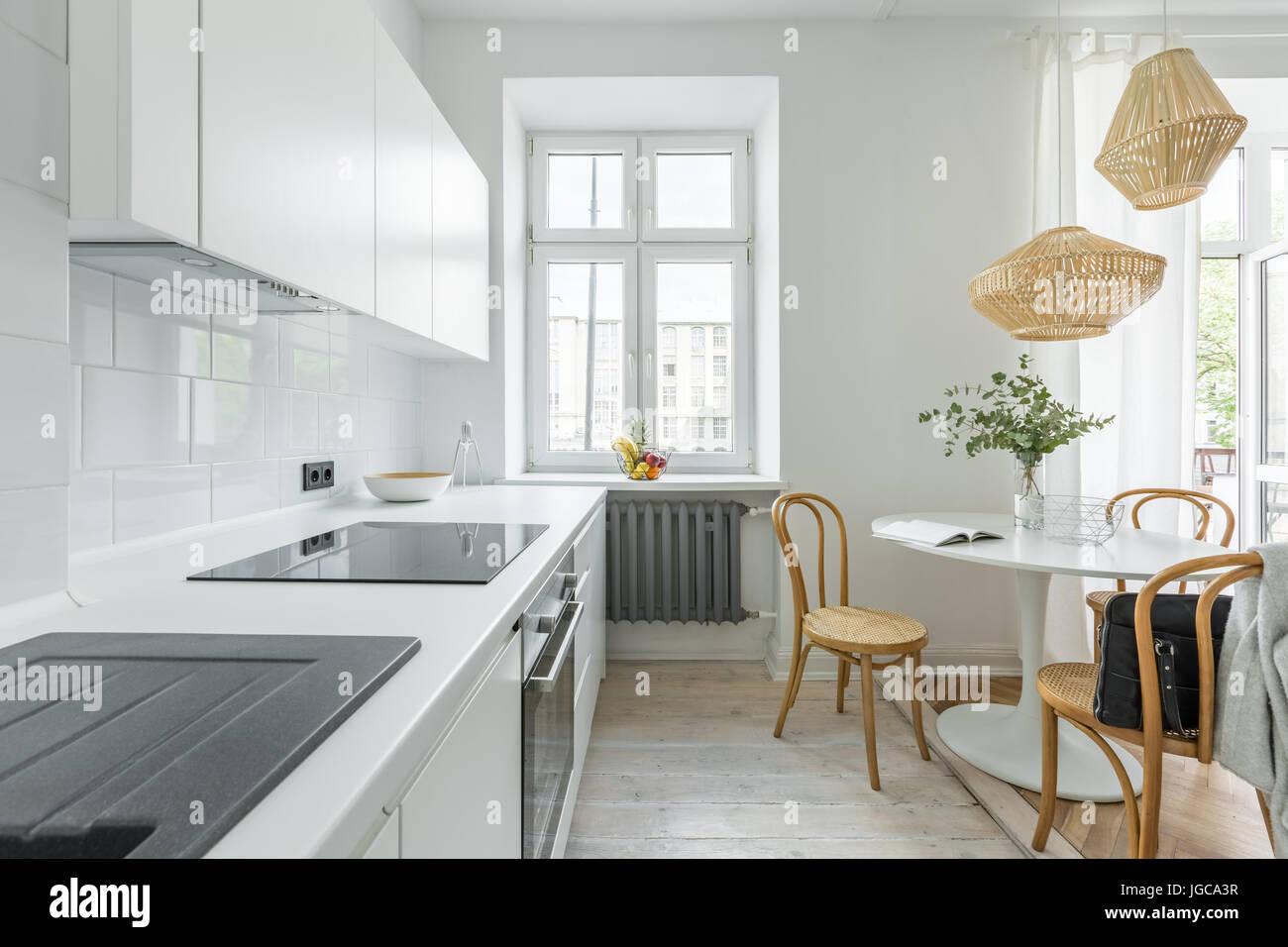 Cucina bianca in stile scandinavo con tavolo rotondo e sedie ...