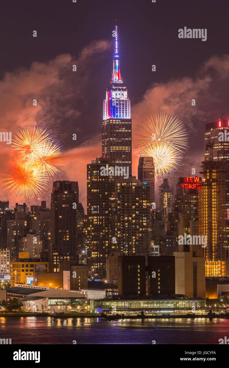 L annuale Macy's quarta di luglio mostra fuochi d'artificio illumina il cielo dietro la skyline di Manhattan Immagini Stock