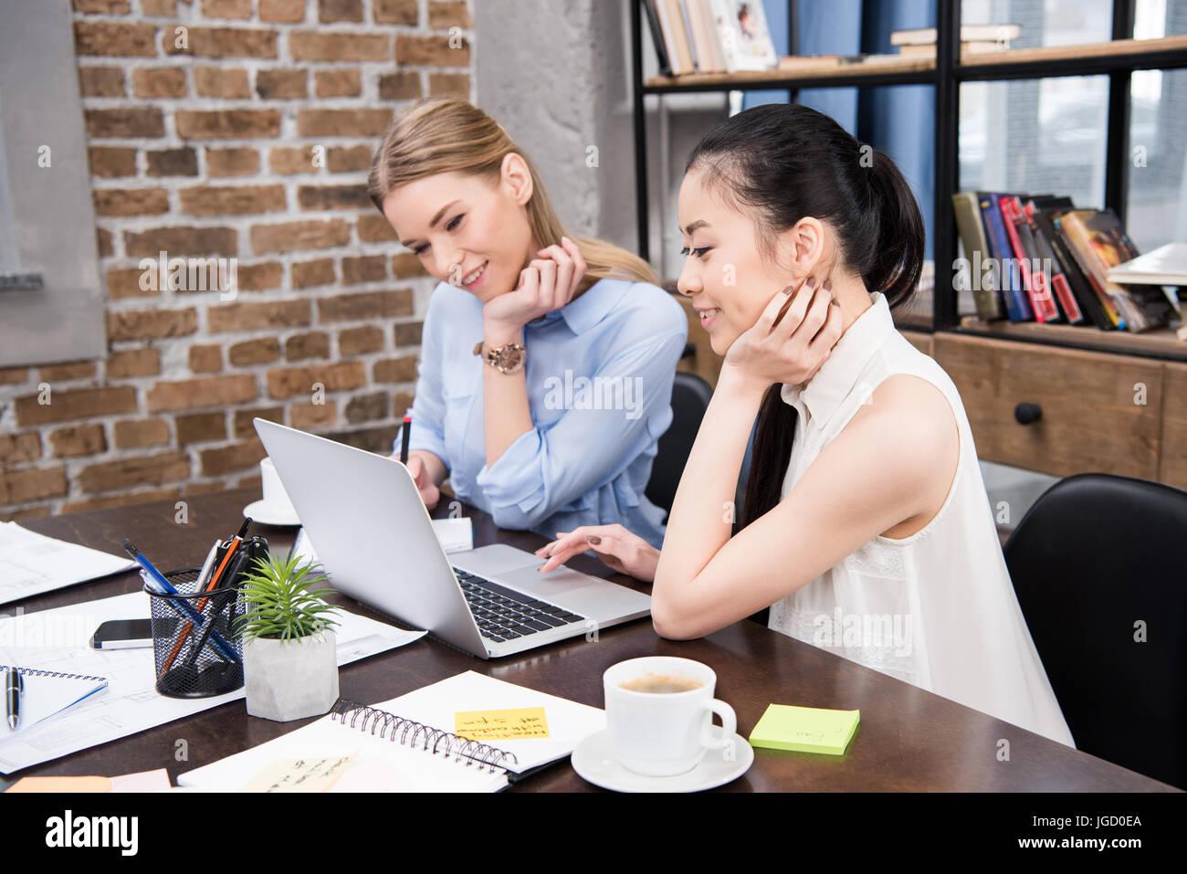 Sorridente imprenditrici multiculturale lavora con laptop e seduti al posto di lavoro Immagini Stock