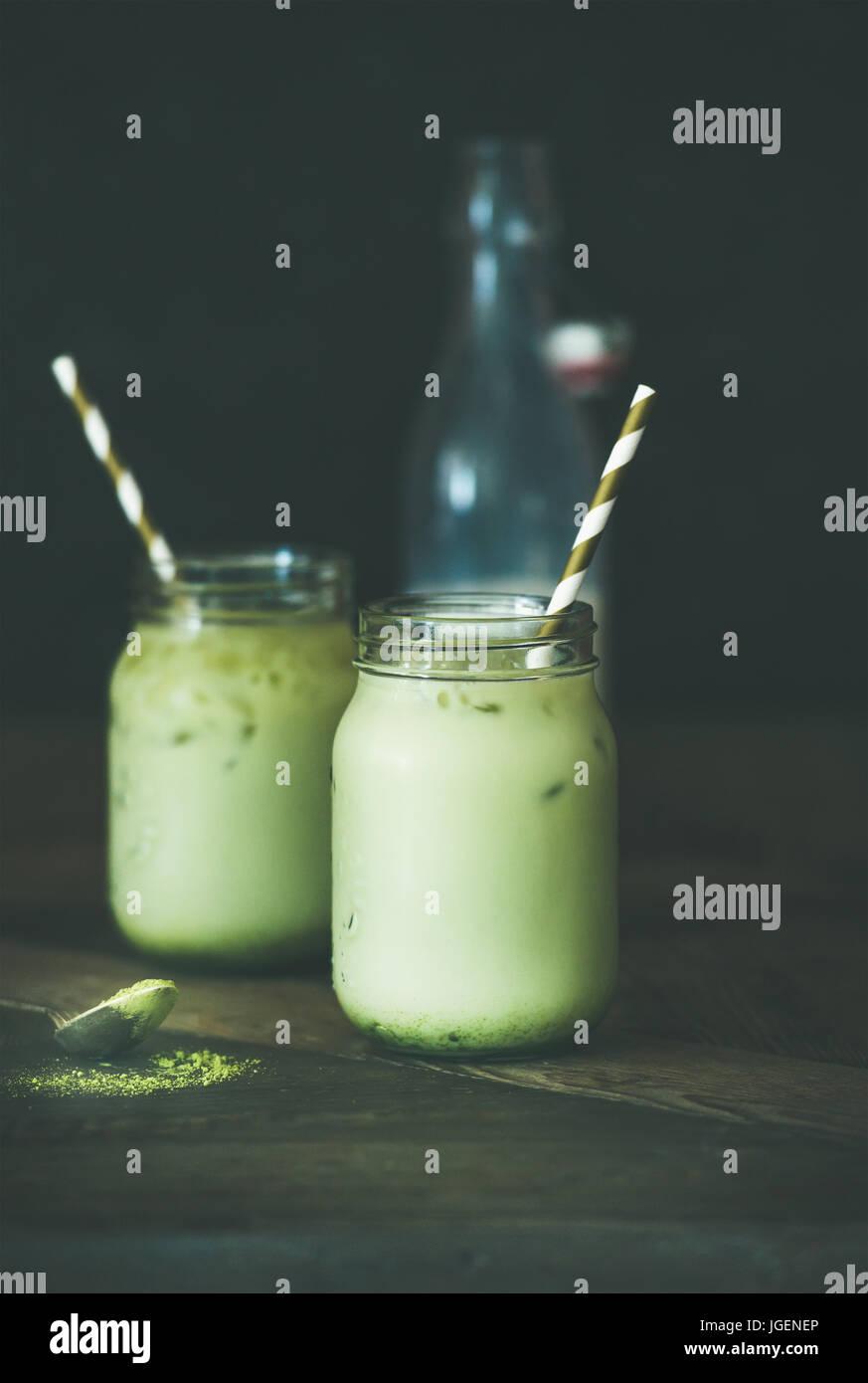 Rinfrescante cocco ghiacciato matcha latte bere in vasi, tavolo in legno Immagini Stock