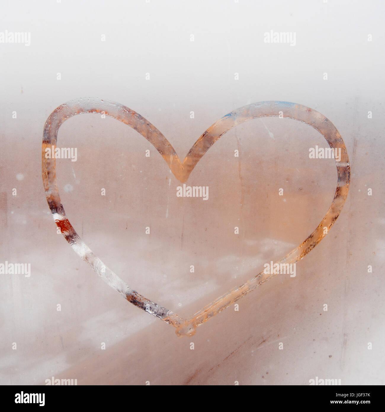 Cuore dipinta su una finestra atomizzata. In autunno la pioggia, l'iscrizione sul vetro sudate - l'amore e il cuore. Foto Stock