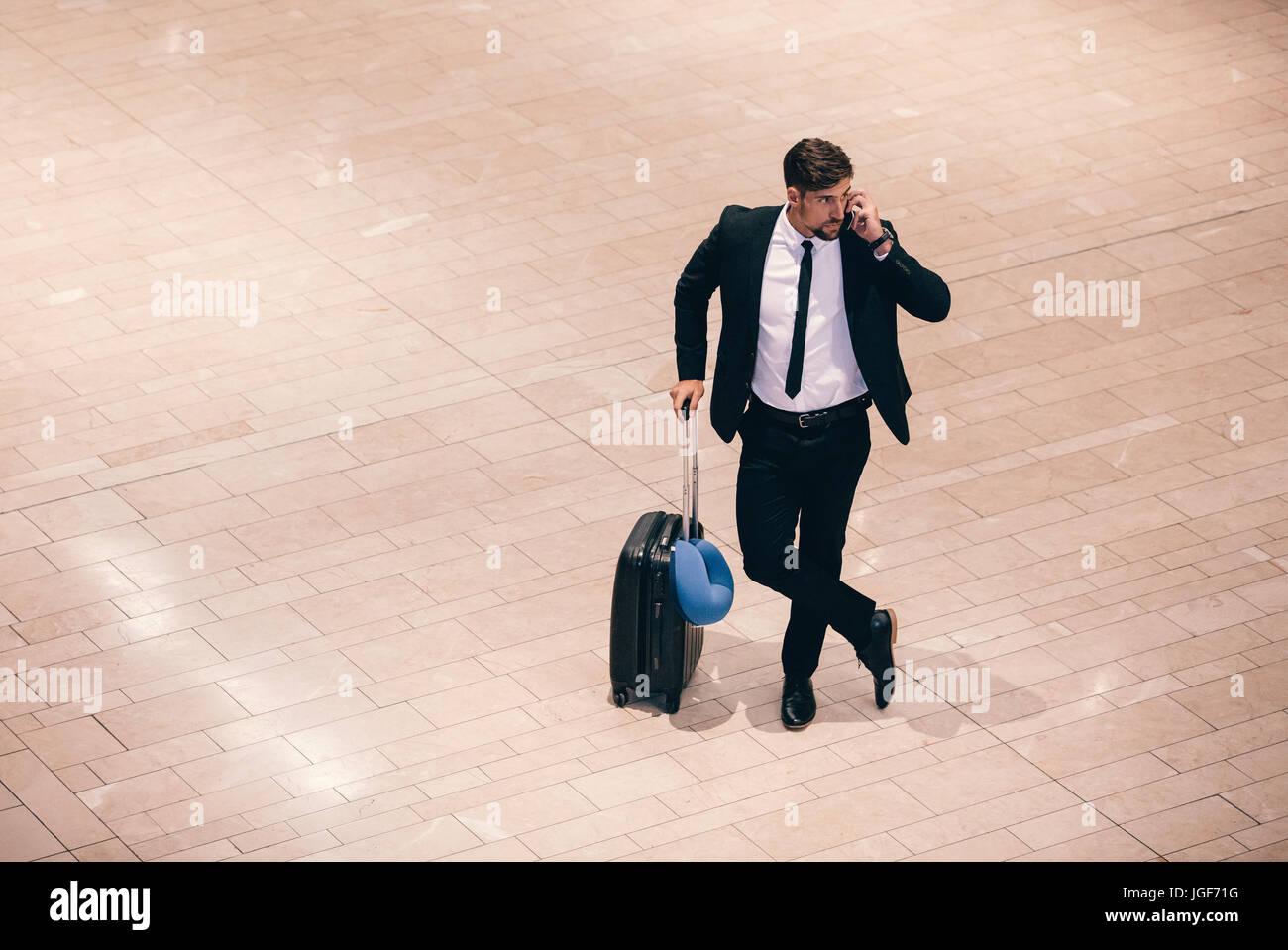 Vista Top Shot del giovane imprenditore permanente al terminal aeroportuale con la valigia e parlando al telefono. Immagini Stock