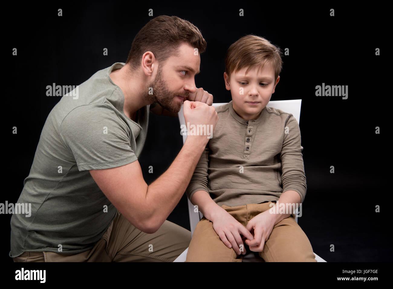 Arrabbiato padre minaccioso e gesti di paura piccolo figlio seduti su una sedia, problemi familiari concetto Immagini Stock