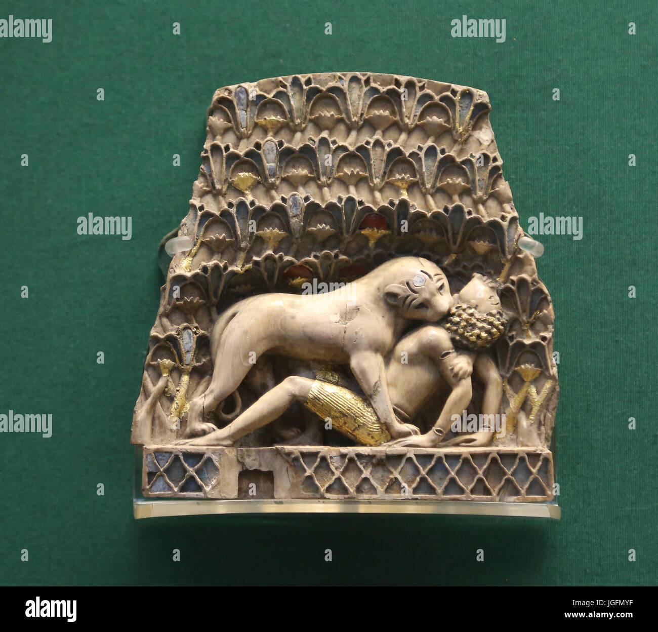 La placca d'Avorio che raffigura un leone divorando un essere umano. Nimrud. Il IX e il VII secolo A.C. Nimrud, Immagini Stock
