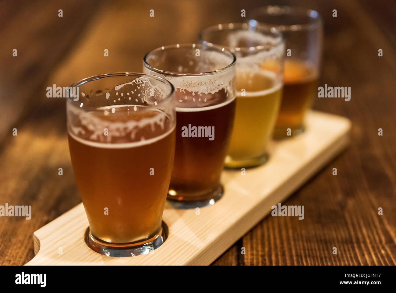 Un assortimento di birra artigianale dei campioni a una micro-birreria. Foto Stock