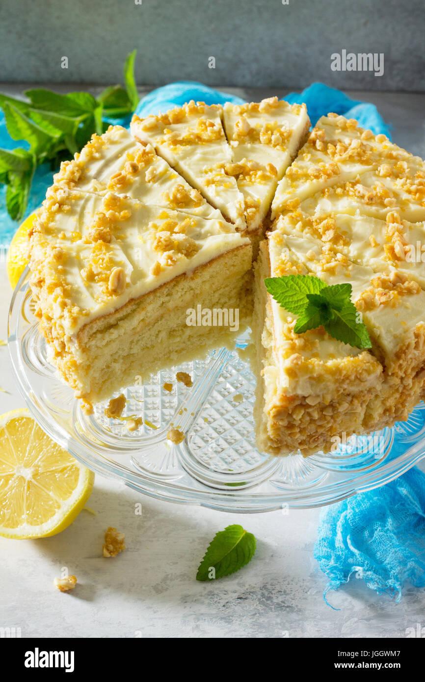 La deliziosa torta di compleanno biscotti al limone e crema di burro, noci tostate. Serve una tavola festiva. Immagini Stock