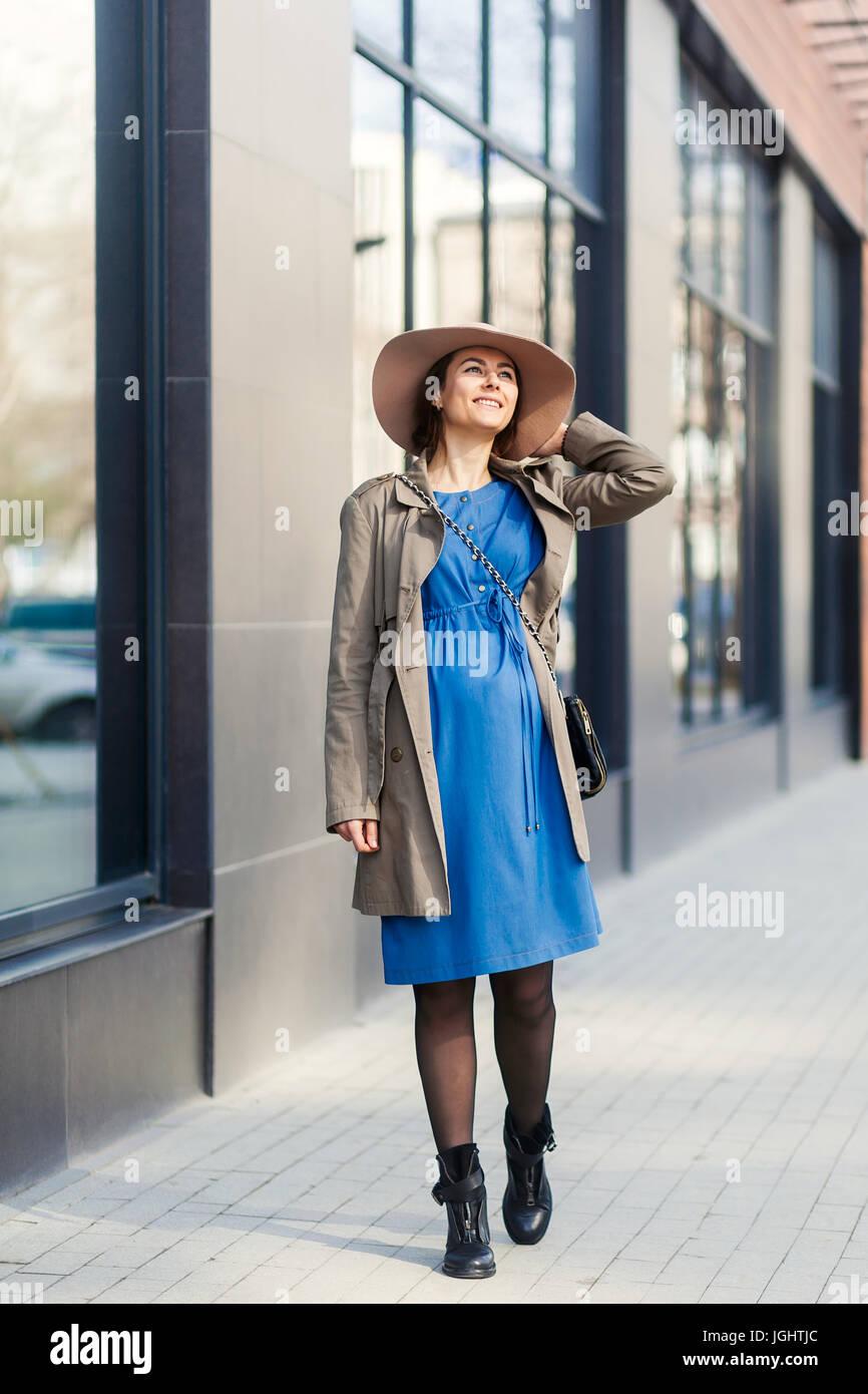 82a3381223bf Le tendenze della moda per donne in stato di gravidanza. moderna donna  incinta in blu abiti comodi e beige hat