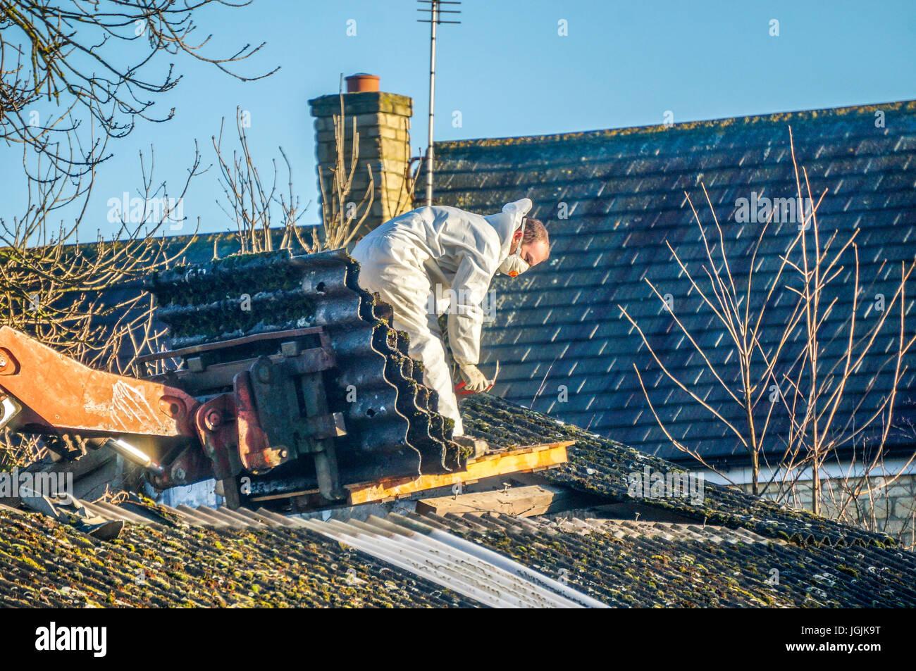 Un uomo che indossa indumenti protettivi durante la rimozione delle coperture in amianto da un vecchio fienile. Foto Stock
