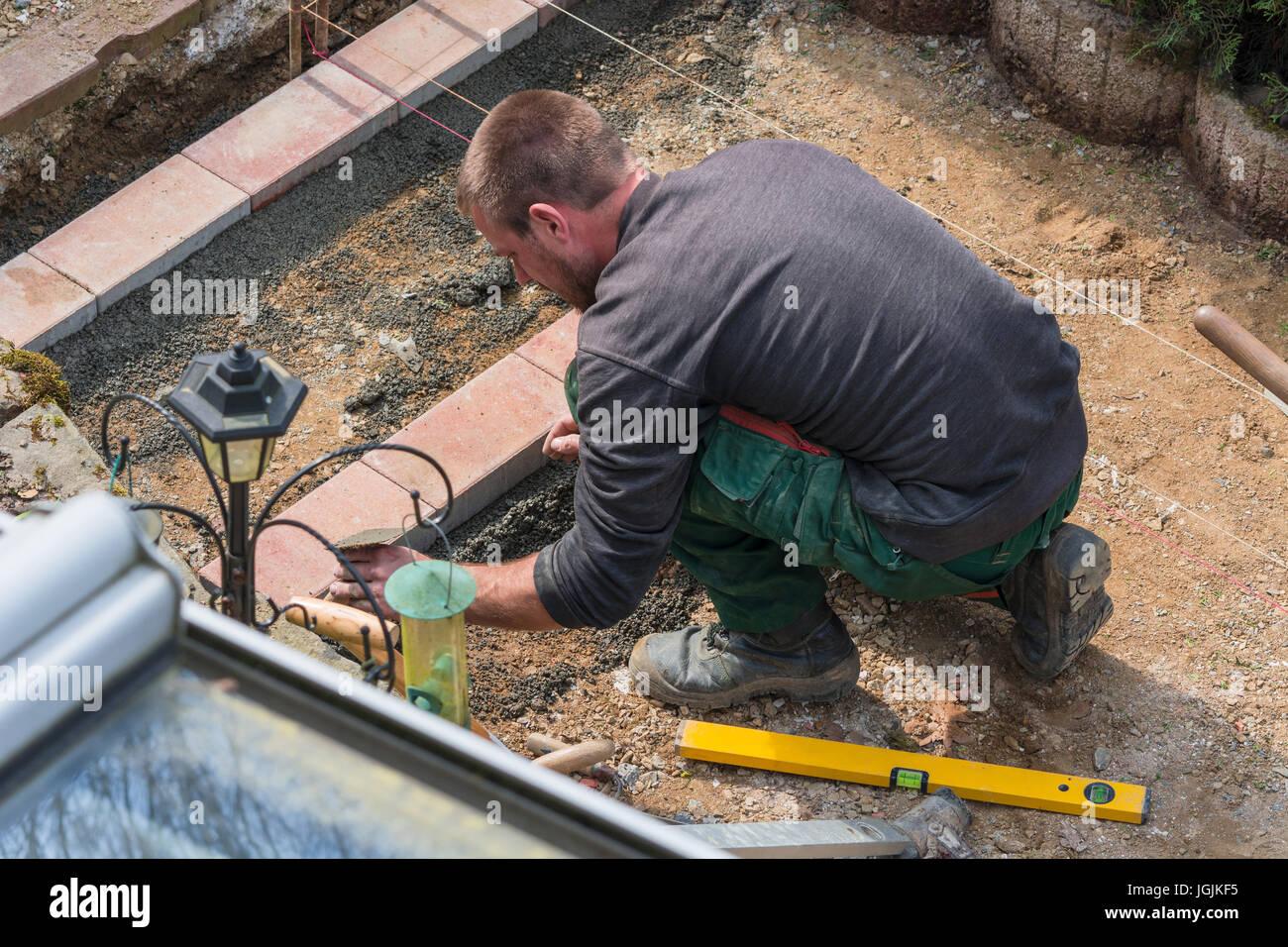 I lavoratori in anticipo per la posa di pavimentazioni pietre e mattoni. Vari strumenti in background. Immagini Stock