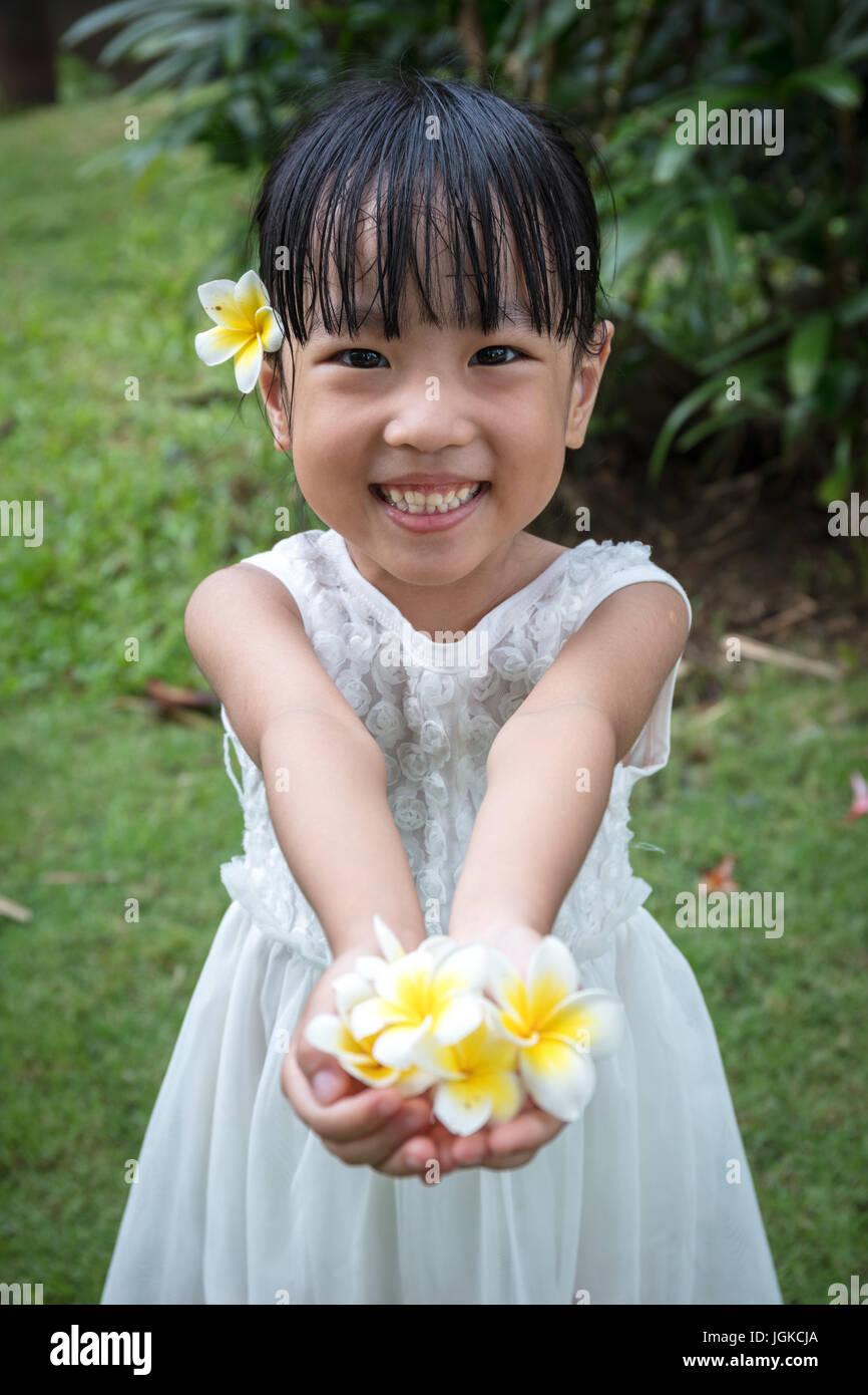 Cinese asiatici poco ragazza con fiori nel giardino esterno sul tempo di giorno Immagini Stock