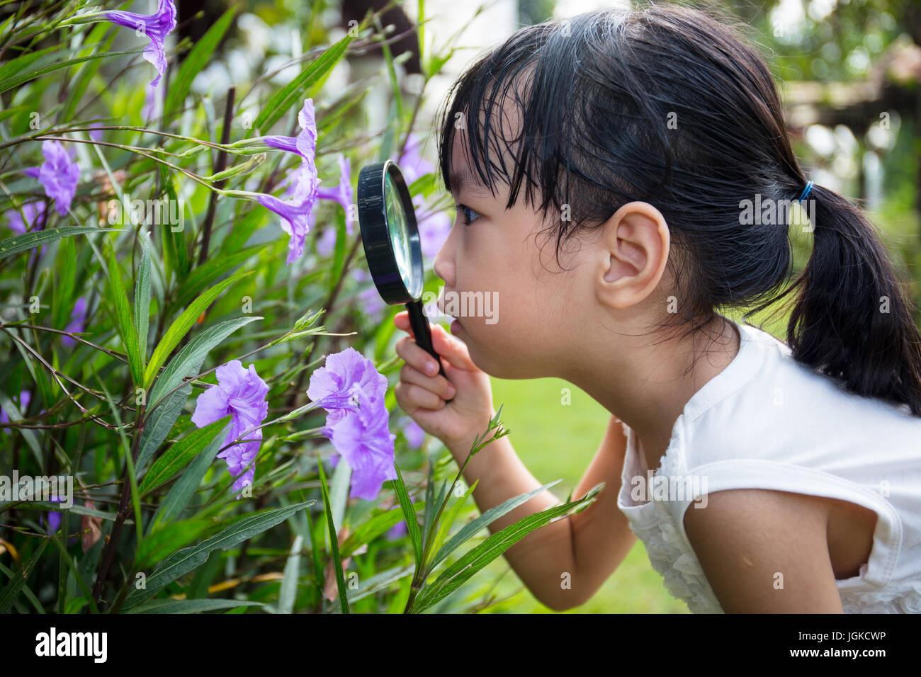 Cinese asiatici bambina guardando fiore attraverso una lente di ingrandimento nel giardino esterno Immagini Stock