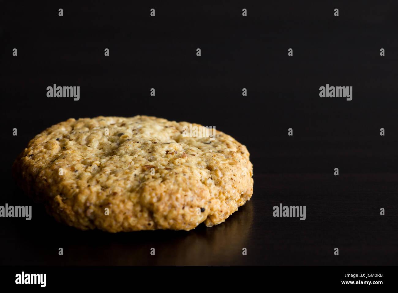 In casa singola di farina di avena cookie, dessert sano, su sfondo scuro. Copia dello spazio. Messa a fuoco selettiva Foto Stock