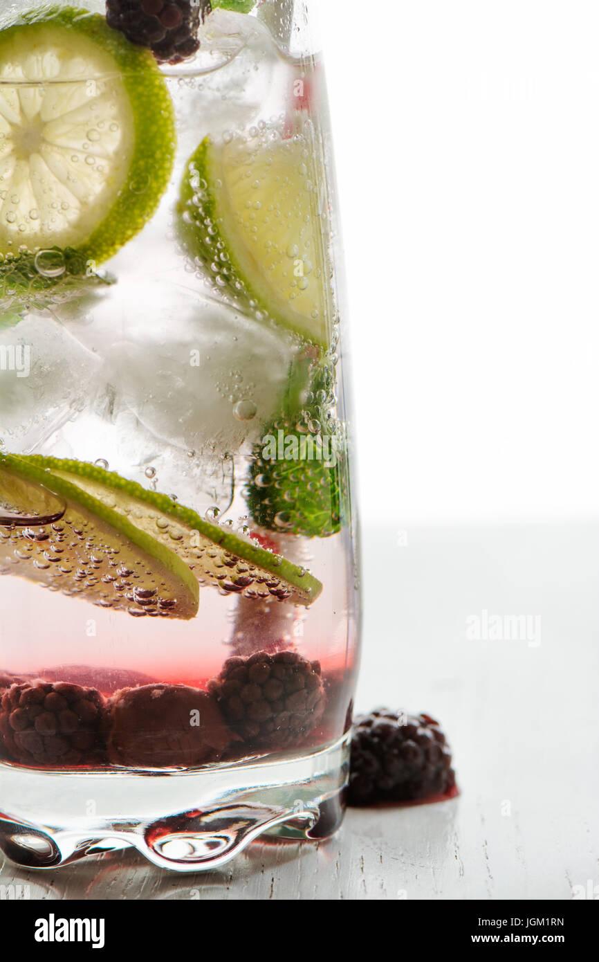 Il gin tonic cocktail con calce, ghiaccio e frutta rossa, sfondo bianco. Close up Immagini Stock