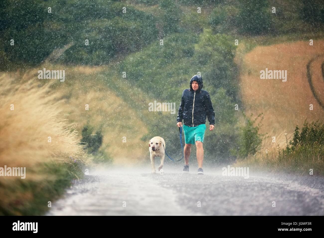 Giovane uomo che cammina con il suo cane (labrador retriever) in heavy rain per la strada rurale. Immagini Stock