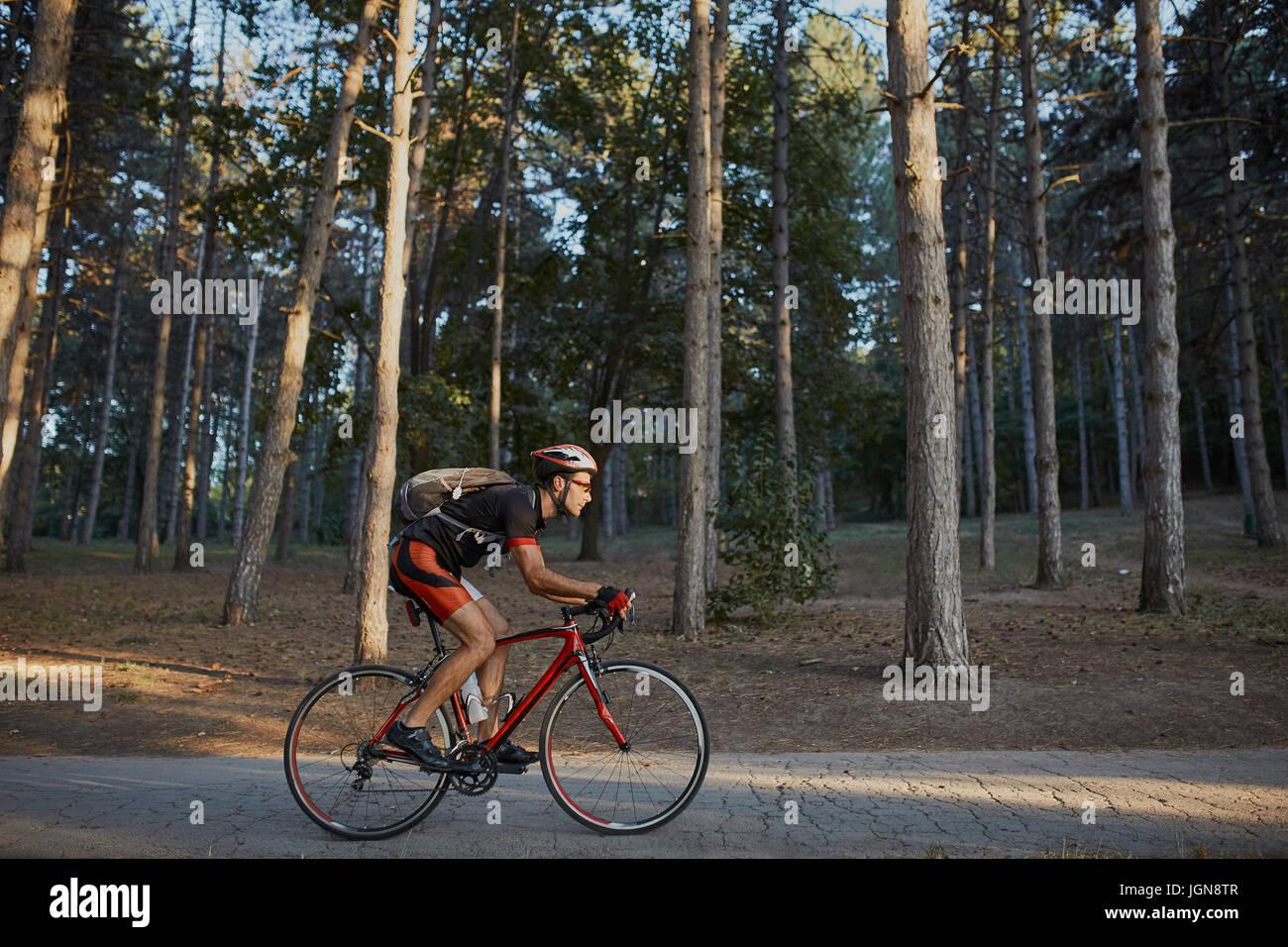 Giovani ed energici ciclista nel parco. L'uomo sono la bicicletta bici da strada e dal lago nel parco Immagini Stock